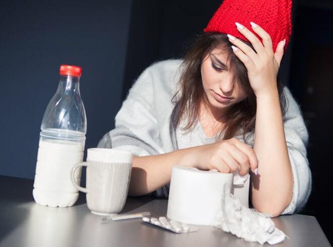 Молодая девушка лечится молоком с содой от простуды