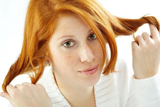 Рыженькая девочка прикрывает веснушки своими волосами