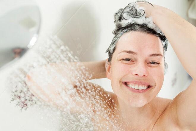 Девушка с улыбкой промывает волосы после лечебной содовой смеси