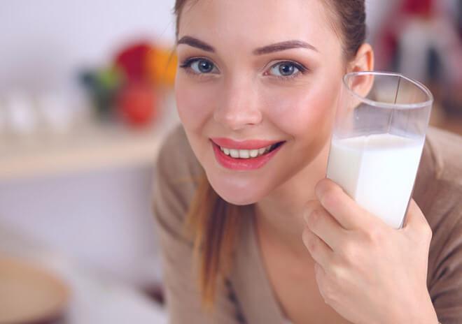 девушка держит стакан с молоком и содой в руке