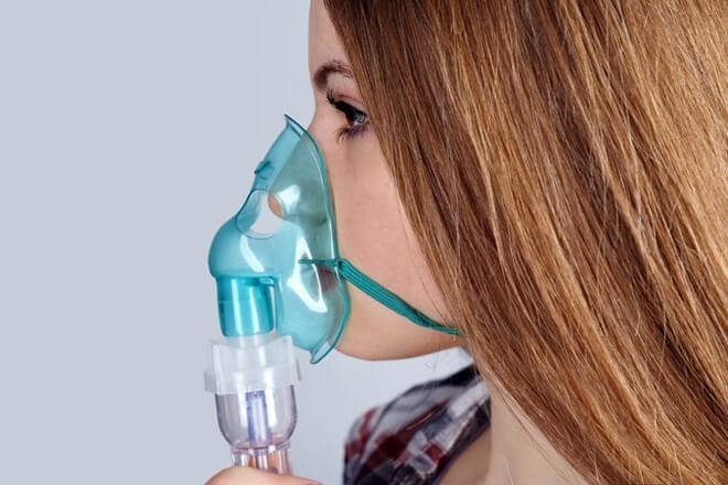 Девушка вдыхает лечебные пары в специальном устройстве