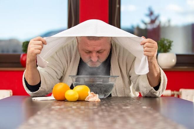 Простуженный мужчина проводит себе ингаляцию в домашних условиях