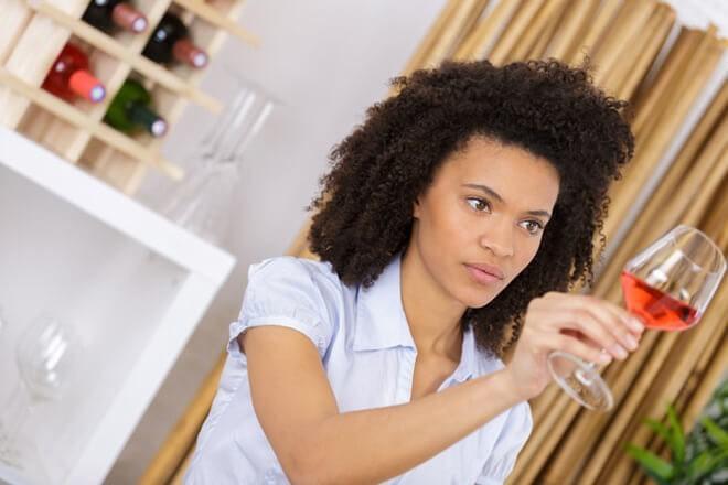 девушка проверяет вино в бокале на свет