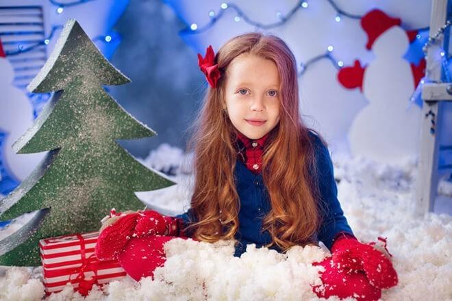 Ребенок среди искусственного снега и рождественских игрушек