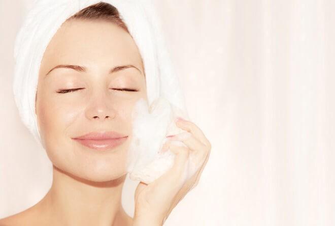 Молодая женщина нежно очищает щеточкой лицо