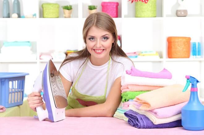 Молодая девушка показывает подошву утюга после чистки