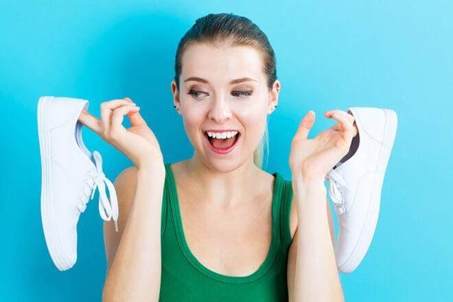 Молодая девушка радостно показывает обновленные кроссовки