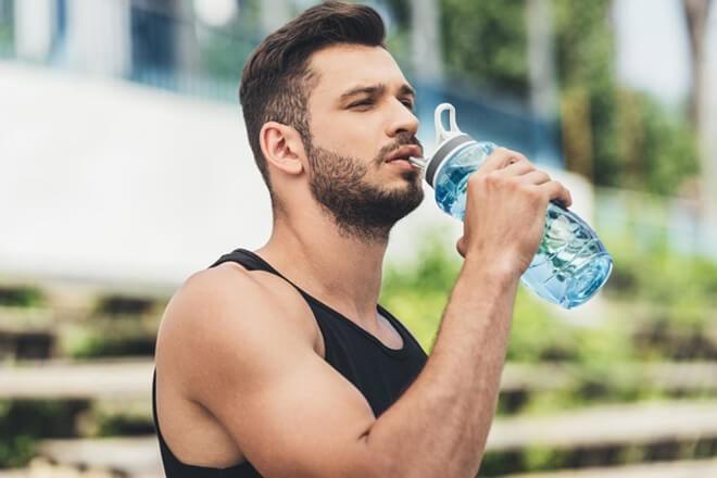 Спортсмен пьёт содовый коктейль