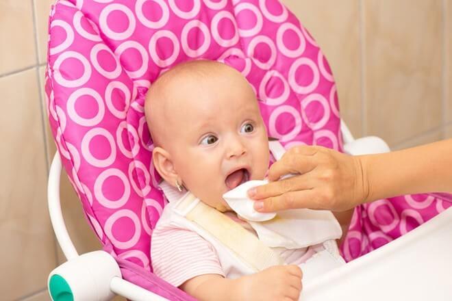 Мама очищает язык у малыша пищевой содой