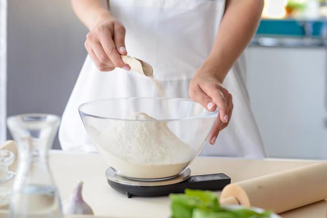 Женщина добавляет разрыхлитель в тесто