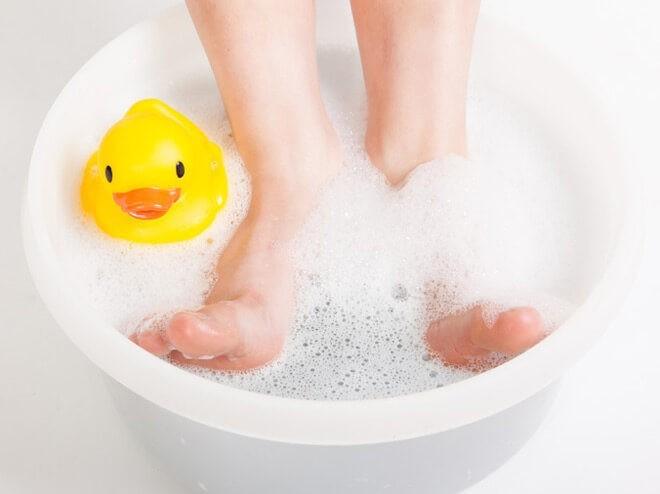 Ножки ребёнка в тёплой ванночке с бикарбонатом натрия